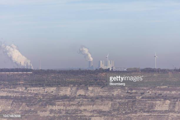 Smoke billows on the horizon from Frimmersdorf left and Neurath coalpowered plants operated by RWE AG beyond the company's open pit lignite mine in...