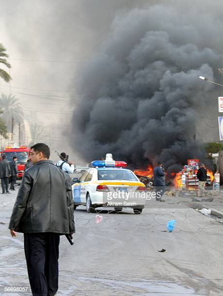 Smoke billows up into the air as Iraqi policemen secure the scene of a car bomb explosion near a Christian church on January 29 2006 in the Karrada...