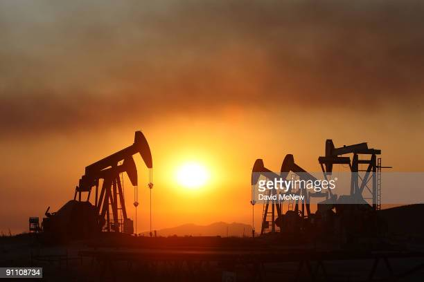 Smoke blows past oil wells at sunset on the eastern flank of the 16000plusacre Guiberson fire burning out of control for a second day as Red Flag...