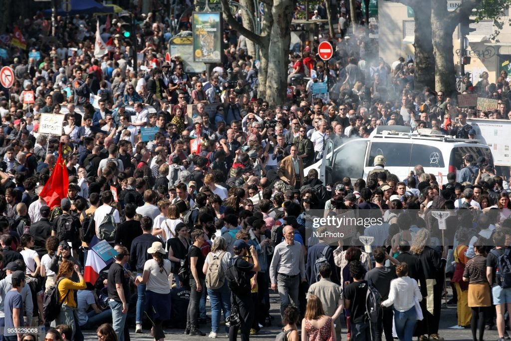 "A smoke bomb is thrown into a vandalised Franceinfo media vehicle as thousands gather during a protest dubbed a ""Party for Macron"" (Fete a Macron) against the policies of the French president on the first anniversary of his election, on May 5, 2018, in Paris"