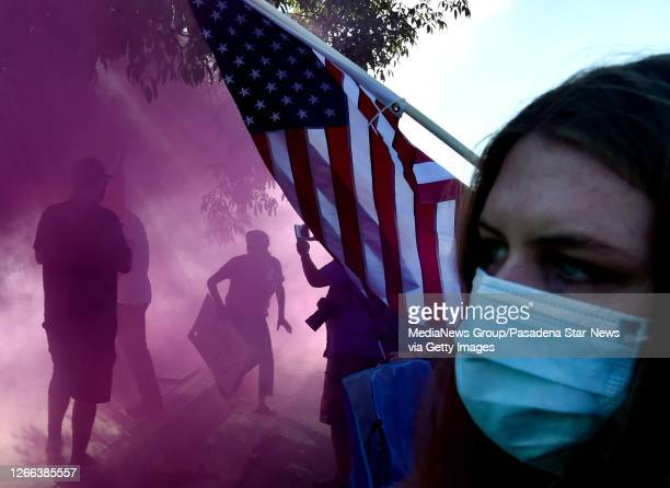 A smoke bomb is tossed as trump supporters fight with Black Lives Matter protestors during a rally by between Black Lives Matter and ProTrump...