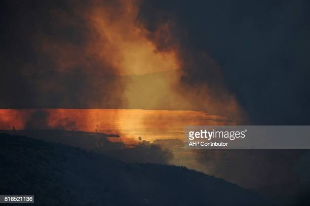 Smoke clouds billow out over the village of Gornje Sitno near the Adriatic coastal town of Split during a fire on July 17 2017 Montenegro asked on...