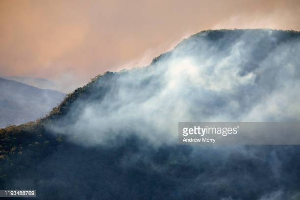 smoke clouds from forest fires drifts in valley and clings to mountain ridge at dusk, blue mountains, australia - moody sky stock pictures, royalty-free photos & images