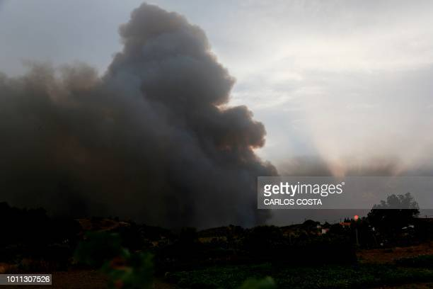 Smoke columns rise due to a wildfire close to Monchique in the Portuguese Algarve, on August 4, 2018. - A village in a tourist area in southern...