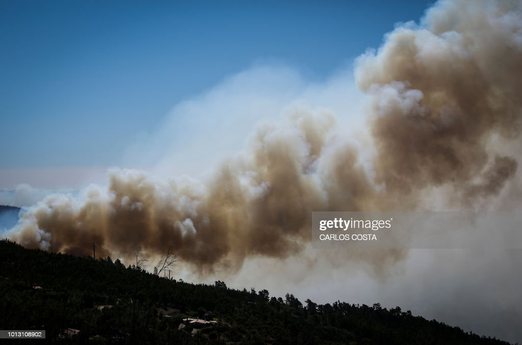 Smoke columns rise due to a wildfire near Monchique, in Algarve, on August 8, 2018. - Spain and Portugal approached record temperatures at the weekend, with the mercury hitting 46.6 degrees Celsius (116 Fahrenheit) at El Granado in Spain and 46.4 C in Alvega, Portugal, according to the World Meteorological Organisation (WMO). While the deadly hot spell is expected to ease in parts of western Europe in the coming days, firefighters in Spain and Portugal struggled to contain wildfires that have swept southern areas.
