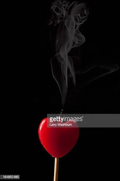 Smoke coming from an extinguished heart shaped candle on a stick