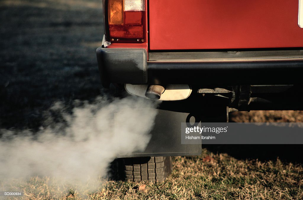 Smoke Coming from Exhaust Pipe of a Car : Stock Photo
