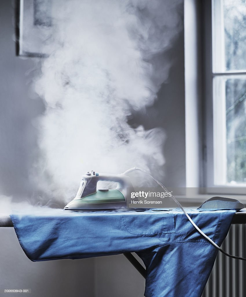 Smoke coming out from unattended iron : Stock Photo