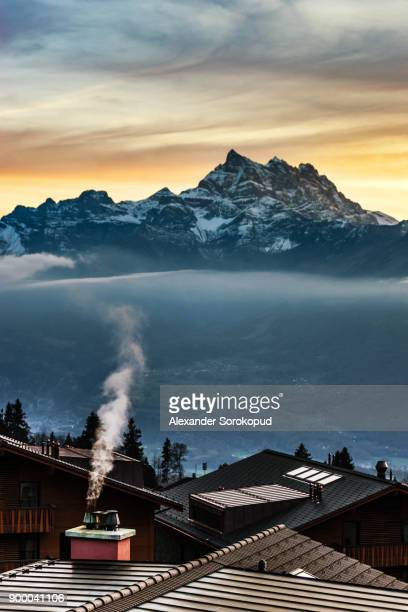 smoke coming out of the chimney house on alpine mountains background, switzerland - kanton waadt stock-fotos und bilder