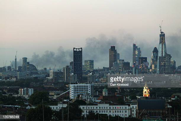 Smoke continues to drift across the London skyline on August 9 2011 in London England Widespread looting arson and clashes with police continued for...