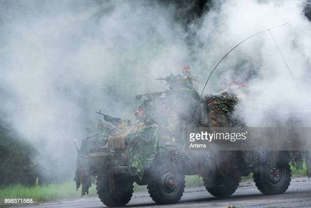 Smoke curtain and Belgian paracommandos of the ParaCommando Regiment under attack in camouflaged LRPV armoured vehicle the MercedesBenz Unimog 404