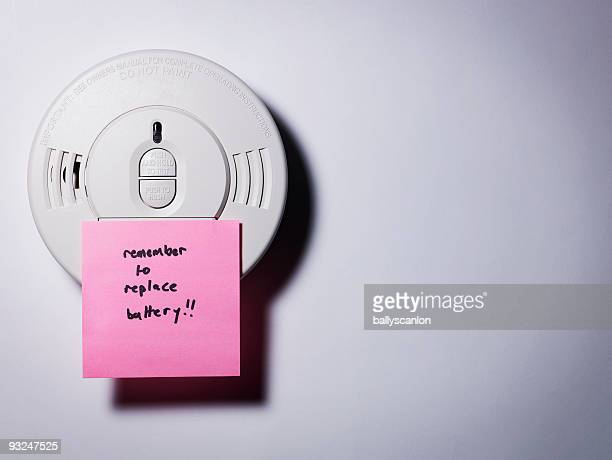 Smoke detector with 'replace the battery' note.