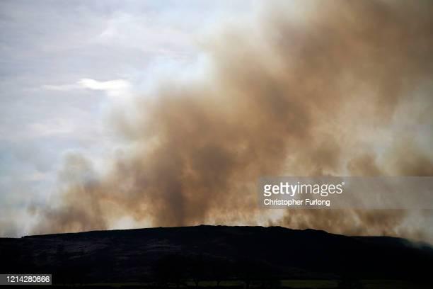 Smoke drifts across moorland as firefighters tackle a grass fire near the village of Marsden on March 23 2020 in Huddersfield England