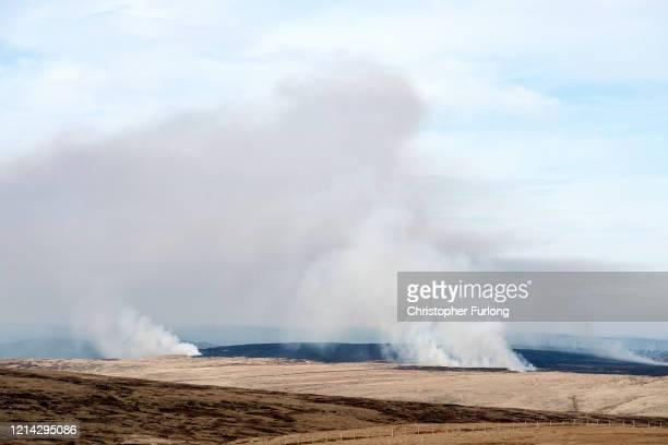 Smoke drifts across moorland as firefighters tackle a grass fire near the village of Marsden on March 23, 2020 in Huddersfield, England.