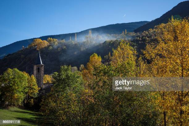Smoke emerges from the mountains as autumncoloured trees are lit by the afternoon sun on October 25 2017 in Gavas Spain Catalonia is one of 17...