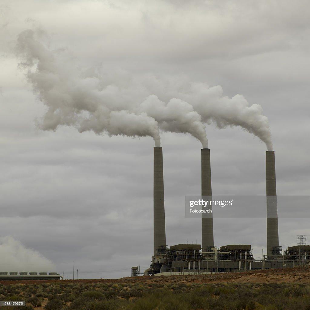 Smoke emerging from chimney stacks : Stock Photo