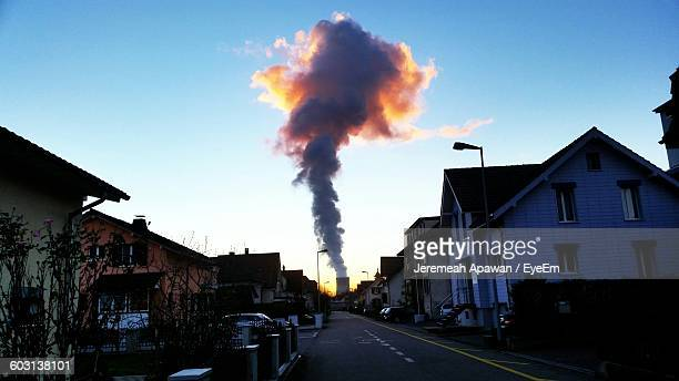 Smoke Emerging From Chimney With Houses Along Road In Foreground