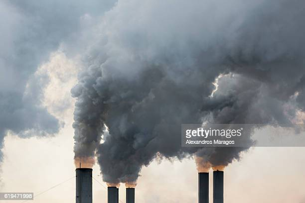 smoke emerging from chimneys - pollution stock pictures, royalty-free photos & images
