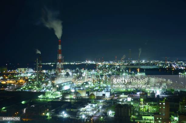 smoke emitting amidst illuminated cityscape against sky at night - mie prefecture stock pictures, royalty-free photos & images
