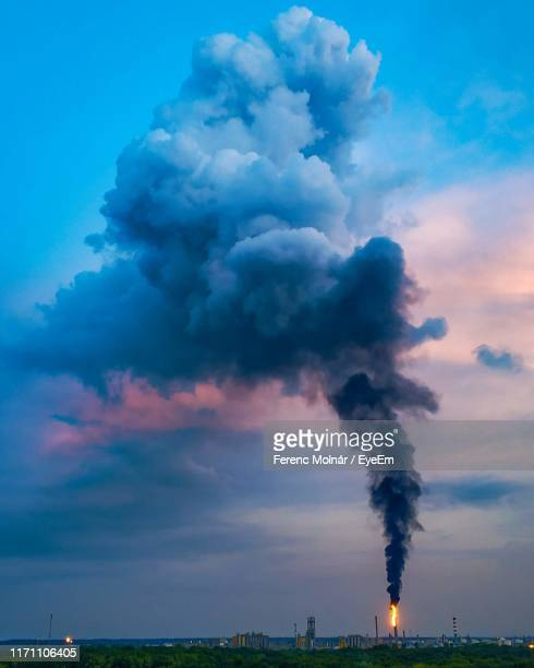 smoke emitting from chimney against cloudy sky - environmental issues stock pictures, royalty-free photos & images