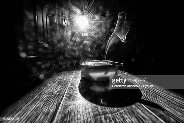 Smoke Emitting From Cigarette On Ashtray At Table Against Bright Sun
