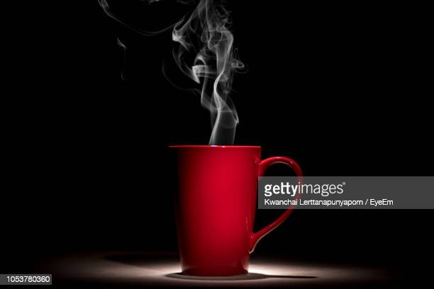 smoke emitting from coffee cup against black background - steam stock pictures, royalty-free photos & images