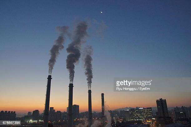 Smoke Emitting From Factories Against Clear Sky At Dusk