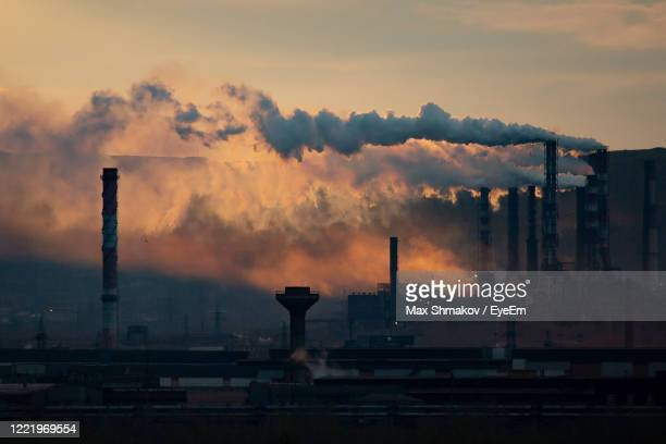 smoke emitting from factory against sky at sunset - russia stock pictures, royalty-free photos & images