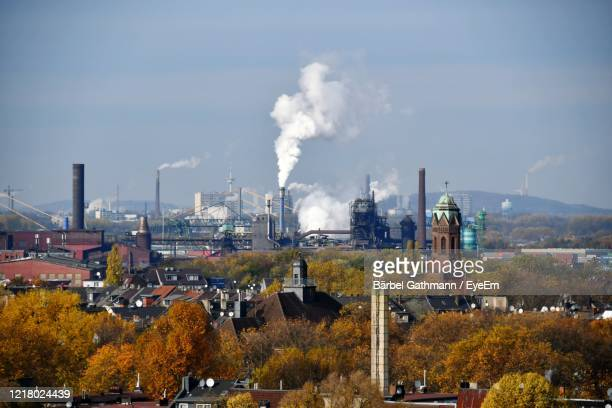 smoke emitting from factory against sky - cooling tower stock pictures, royalty-free photos & images