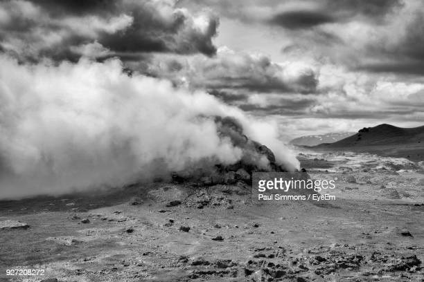 smoke emitting from landscape against cloudy sky - volcanic terrain stock pictures, royalty-free photos & images