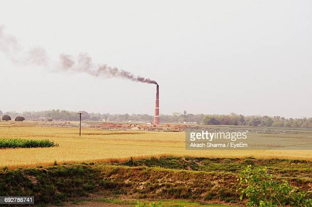 Smoke Emitting From Smoke Stack On Field Against Clear Sky