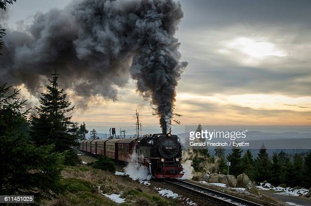 smoke emitting from steam train against cloudy sky during sunset - steam train stock pictures, royalty-free photos & images
