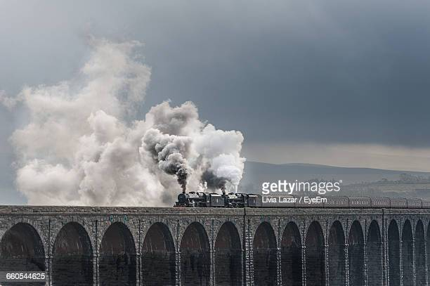 smoke emitting from steam train on bridge against cloudy sky - locomotive stock photos and pictures