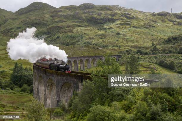 smoke emitting from train on bridge - locomotive stock photos and pictures