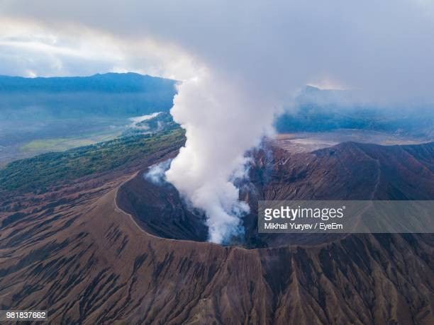 smoke emitting from volcanic crater against sky - cratere vulcano foto e immagini stock
