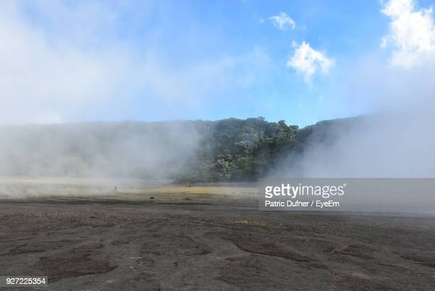 Smoke Emitting From Volcanic Landscape Against Sky