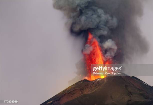smoke emitting from volcanic mountain against sky - active volcano stock pictures, royalty-free photos & images
