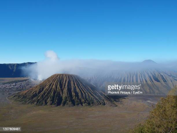 smoke emitting from volcanic mountain against sky - bromo tengger semeru national park stock pictures, royalty-free photos & images