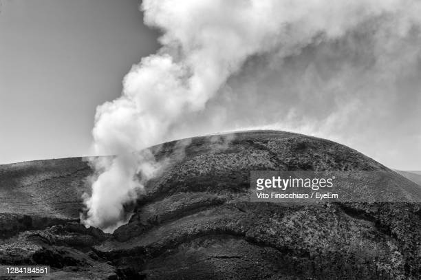smoke emitting from volcanic mountain against sky - 噴出 ストックフォトと画像