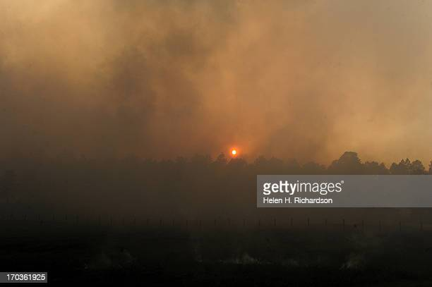 Smoke filled sky obscures the sun as the Black Forest Fire advances towards Herring Road in the Black Forest northeast of Colorado Springs CO on June...