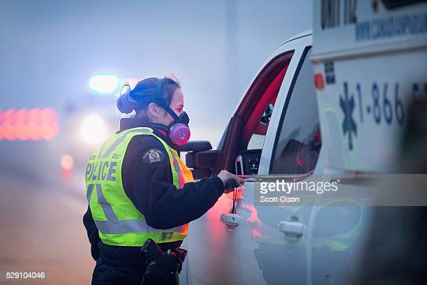 Smoke fills the air as a police officer checks vehicles at a roadblock along Highway 63 leading into Fort McMurray on May 8 2016 near Fort McMurray...
