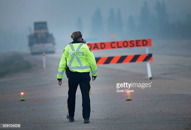 Smoke fills the air as a police officer stands guard at a roadblock along Highway 63 leading into Fort McMurray on May 8 2016 near Fort McMurray...