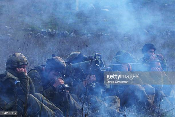 Smoke fills the air as Israeli army paratroopers fire an antitank missile during their training exercise December 10 2009 on the Golan Heights The...