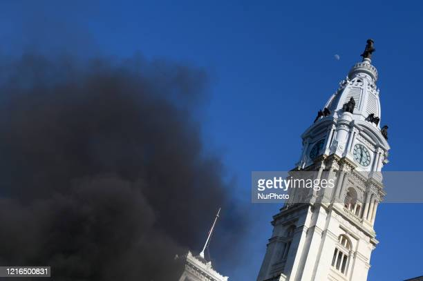 Smoke from a burning police car billows up as protestors clash with police near City Hall in Philadelphia PA on May 30 2020 Cities around the nation...