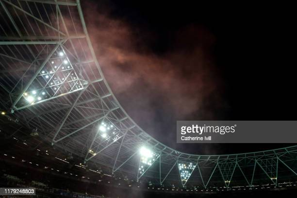 Smoke from a flare in the lights during the Premier League match between West Ham United and Crystal Palace at London Stadium on October 05 2019 in...