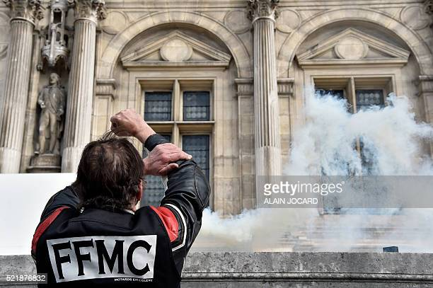 Smoke from a flare rises near a man wearing a 'Federation Francaise des Motards en Colere' vest and gesturing obscenely as bikers demonstrate in...