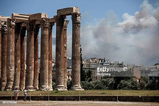 Smoke from a forest fire on the eastern outskirts of the city covers the skyline beyond the temple of Olympian Zeus in Athens Greece on Friday July...