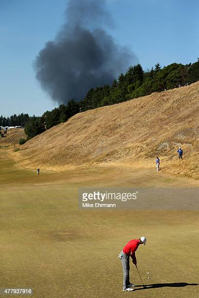 Smoke from a local fire is seen above as Jordan Spieth of the United States putts on the eighth green during the third round of the 115th US Open...