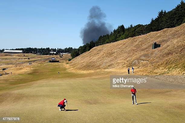 Smoke from a local fire is seen above Patrick Reed and Jordan Spieth of the United States on the eighth green during the third round of the 115th US...