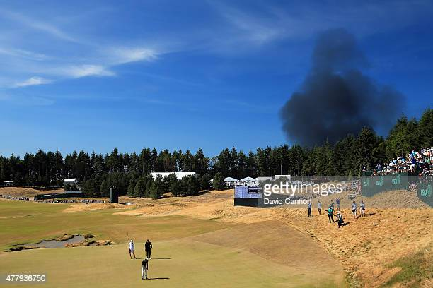 Smoke from a local fire is seen above the 13th green during the third round of the 115th U.S. Open Championship at Chambers Bay on June 20, 2015 in...